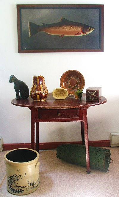 booth image: table with ceramics and fish painting